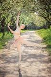Młody baletniczy tancerz pokazuje klasyczne balet pozy outdoors przy słońcem Obrazy Royalty Free