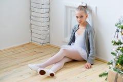 Młody baletniczy tancerz siedzi blisko choinki obraz royalty free