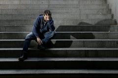 Młody bezdomny mężczyzna gubił pracę w kryzysu cierpienia depresji obsiadaniu na zmielonych ulica betonu schodkach zdjęcie royalty free