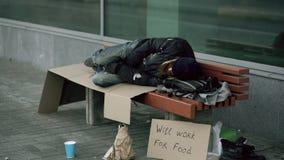 Młody bezdomny pijący obsługuje narządzanie spać na kartonie na ławce przy chodniczkiem zbiory