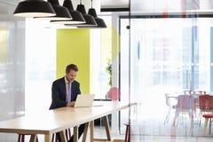 Młody biały człowiek pracuje samotnie w biurowym spotyka terenie fotografia stock