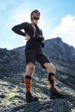 Młody biały męski turysta stoi na skale w górach w sportswear i butach zdjęcia stock