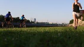 Młody biegacz dziewczyny bieg przez zieloną trawę zbiory
