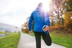 Młody biegacz w jesień parka pozyci na betonowej ścieżce obraz royalty free