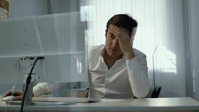 Młody biurowy mężczyzny pracownika obsiadanie z rękami na głowie przed komputerem zdjęcie wideo