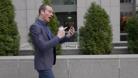 Młody biznesmen chodzi z bezprzewodowymi słuchawkami i agresywnie prowadzi dyskusję na wideo wzywa smartphone zbiory