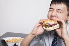 Młody biznesmen cieszy się hamburger Fotografia Royalty Free