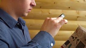 Młody biznesmen czyta gazetę z powiększać - szkło zbiory