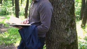 Młody biznesmen czyta książkę w drewnach blisko drzewa zbiory