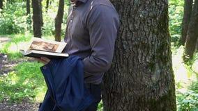 Młody biznesmen czyta książkę w drewnach blisko drzewa zdjęcie wideo