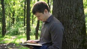 Młody biznesmen czyta książkę w drewnach blisko drzewa zbiory wideo