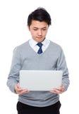 Młody biznesmen czytający na notebooku Obrazy Stock