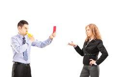 Młody biznesmen dmucha wistle i pokazuje czerwoną kartkę jego Fotografia Stock