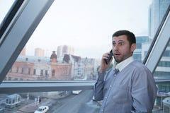 Młody biznesmen emocjonalnie opowiada na telefonie komórkowym z zdziwieniem na jego twarzy przeciw tłu panoramiczny okno fotografia royalty free