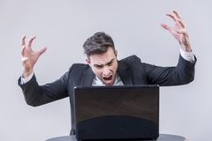 Młody biznesmen gniewny z jego laptopem fotografia royalty free