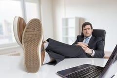 Młody biznesmen jest relaksujący przy miejscem pracy i jego cieki na biurku w biurze Zdjęcie Stock