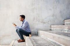 Młody biznesmen Jest usytuowanym na schodku podczas gdy Pracujący na Digital stole fotografia stock