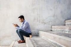 Młody biznesmen Jest usytuowanym na schodku podczas gdy Pracujący na Digital stole obraz stock