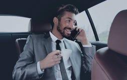 Młody biznesmen ma kawę w jego samochodzie Obrazy Stock