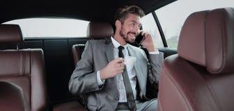 Młody biznesmen ma kawę w jego samochodzie Obraz Stock