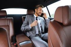 Młody biznesmen ma kawę w jego samochodzie Obraz Royalty Free