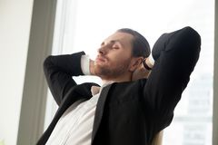Młody biznesmen odpoczywa przy pracą z jego rękami za głową zdjęcia royalty free