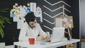 Młody biznesmen opowiada na telefonie komórkowym z laptopem i pisze puszek notatkach zdjęcie wideo