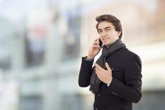 Młody biznesmen opowiada telefon komórkowego na ulicie Fotografia Stock