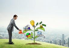 Młody biznesmen outdoors nawadnia rysującego wzrostowego pojęcie z puszką Fotografia Stock