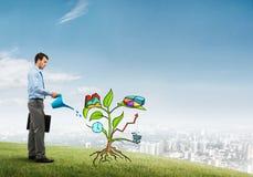 Młody biznesmen outdoors nawadnia rysującego wzrostowego pojęcie z puszką Obrazy Stock