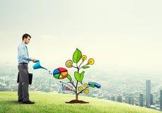 Młody biznesmen outdoors nawadnia rysującego wzrostowego pojęcie z puszką Zdjęcia Royalty Free