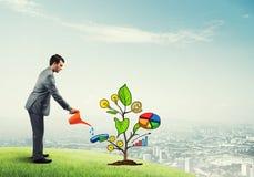 Młody biznesmen outdoors nawadnia rysującego wzrostowego pojęcie z puszką Obraz Royalty Free