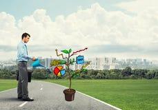 Młody biznesmen outdoors nawadnia rysującego wzrostowego pojęcie z puszką Zdjęcie Stock