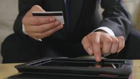Młody biznesmen płaci rachunki i używa online bankowość na pastylka komputerze osobistym zbiory