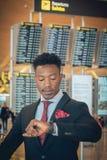 Młody biznesmen patrzeje jego mądrze zegarek w lotnisku w f fotografia stock