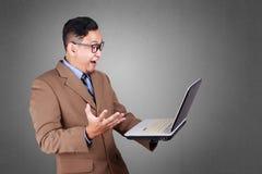Młody biznesmen Patrzeje laptop, Zdziwiony wyrażenie zdjęcie royalty free