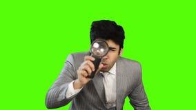 Młody biznesmen patrzeje przez powiększać - szkło na zielonym tle zbiory wideo
