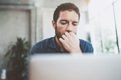 Młody biznesmen pracuje przy nowożytnym loft biurem Zadumany mężczyzna obsiadanie i używać współczesnego laptop zamazujący tło Zdjęcie Stock