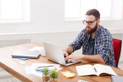 Młody biznesmen pracuje z laptopem w nowożytnym białym biurze Fotografia Royalty Free