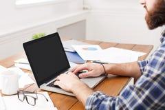Młody biznesmen pracuje z laptopem w nowożytnym białym biurze Obraz Stock