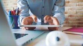 Młody biznesmen pracuje z pastylką i pisać na maszynie na wirtualnej klawiaturze w jego biurze przy miejscem pracy zdjęcie wideo