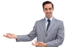 Młody biznesmen przedstawia coś z jego ręki Fotografia Stock