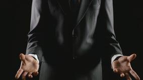 Młody biznesmen przedstawia i wyjaśnia na czarnym tle zbiory