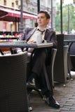 Młody biznesmen przychodził jeść lunch w kawiarni, siedzi przy stołem i czeka someone zdjęcia royalty free