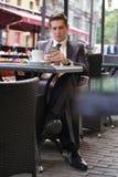 Młody biznesmen przychodził jeść lunch w kawiarni, siedzi przy stołem i czeka someone obraz royalty free