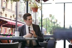 Młody biznesmen przychodził jeść lunch w ulicznej kawiarni, siedzi przy stołem i ciągnie out kiesy płacić rachunek obrazy stock