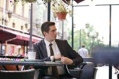 Młody biznesmen przychodził jeść lunch w ulicznej kawiarni, siedzi przy stołem i ciągnie out kiesy płacić rachunek zdjęcie stock