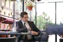 Młody biznesmen przychodził jeść lunch w ulicznej kawiarni, siedzi przy stołem i ciągnie out kiesy płacić rachunek obraz stock