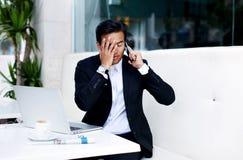 Młody biznesmen rozczarowywający z złą wiadomością podczas telefon rozmowy nakrycia twarzy z jego ręką Fotografia Royalty Free