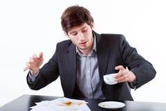 Młody biznesmen rozlewa kawę dla dokumentów Obrazy Stock